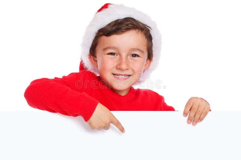 Dziecko dzieciak Bożenarodzeniowy Święty Mikołaj wskazuje szczęśliwą pustą sztandar kopię zdjęcie royalty free