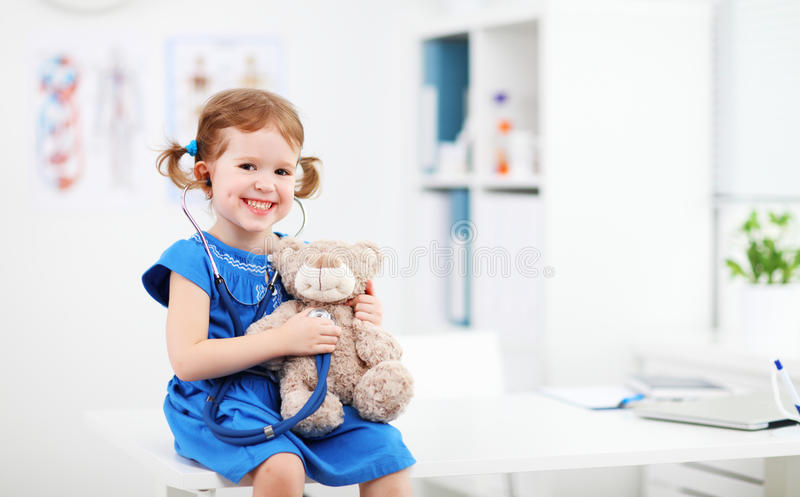 Dziecko dziewczyna bawić się lekarkę z misiem obrazy stock