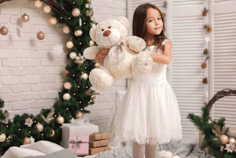 Dziecko dziewczyna bawić się z misiem blisko choinki obrazy stock