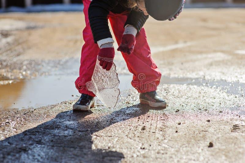 Dziecko dziewczyna bawić się z stapianie lodem na spacerze w zimie zdjęcie royalty free