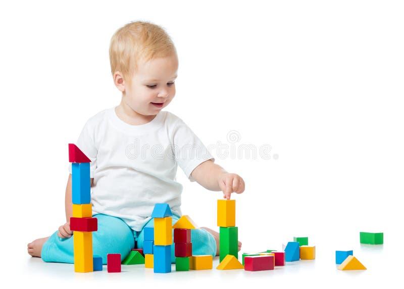 Dziecko dziewczyna bawić się zabawkarskich sześciany odizolowywających na bielu obraz royalty free