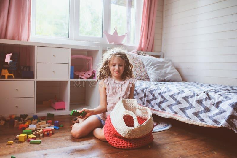 Dziecko dziewczyna czyści jej pokój i organizuje drewniane zabawki w trykotową składową torbę zdjęcie stock