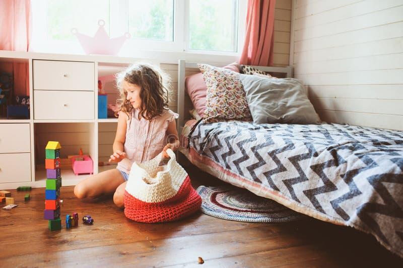 Dziecko dziewczyna czyści jej pokój i organizuje drewniane zabawki w trykotową składową torbę fotografia royalty free