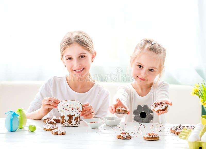 Dziecko dziewczyna dekoruje Wielkanocnych ciastka zdjęcia royalty free