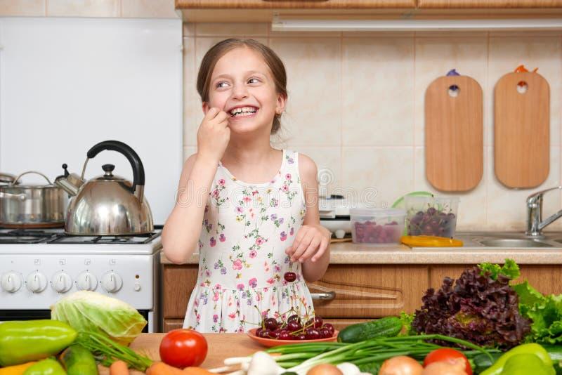 Dziecko dziewczyna je wiśnie, owoc i warzywo w domowej kuchni ja zdjęcia royalty free