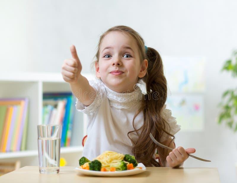 Dziecko dziewczyna je zdrowego karmowego pokazuje kciuk up fotografia stock
