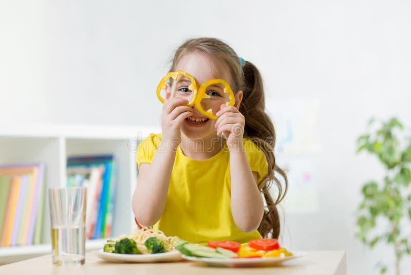 Dziecko dziewczyna ma zabawę z karmowymi warzywami przy kuchnią obrazy stock