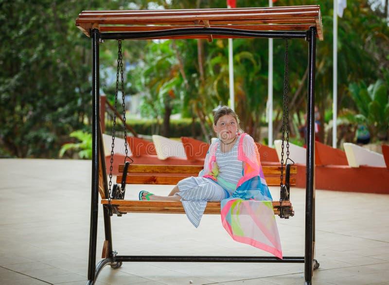 Dziecko dziewczyna na starym roczniku huśta się z zmieszaną reakcją na jej twarzy obraz royalty free