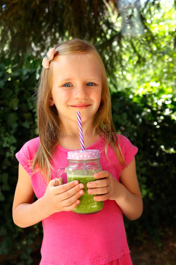 Dziecko dziewczyna pije zdrowego zielonego jarzynowego smoothie - zdrowy łasowania, weganinu, jarosza, żywności organicznej i nap zdjęcia stock