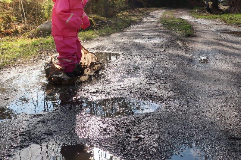 Dziecko, dziewczyna skacze z różowym rainwear/wodnego basenu, kałuży/ fotografia stock