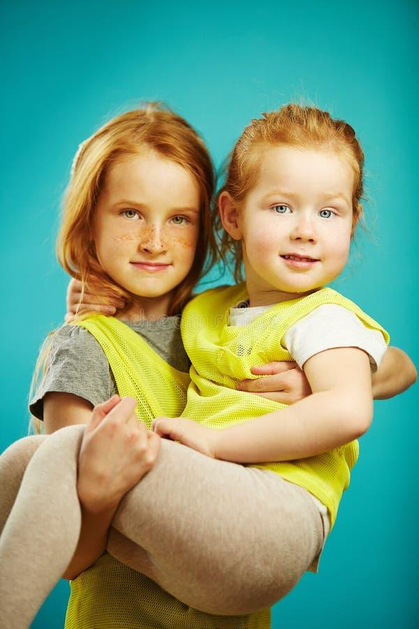 Dziecko dziewczyna trzyma małej siostry na błękitnym odosobnionym tle obrazy royalty free