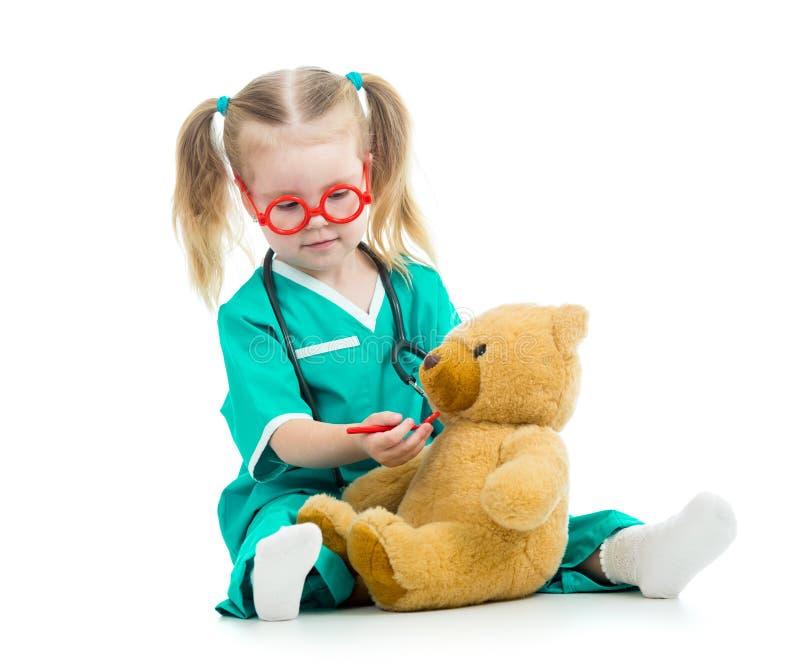 Żartuje dziewczyny bawić się lekarkę z zabawką obraz stock