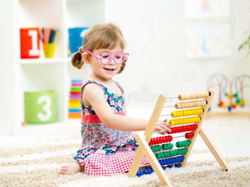 Dziecko dziewczyna z eyeglasses bawić się abakus zabawkę zdjęcia royalty free