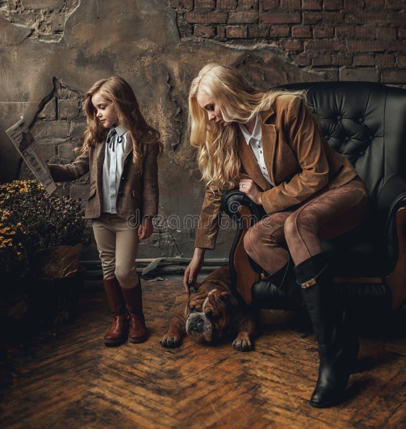Dziecko dziewczyna z kobietą w wizerunku Sherlock Holmes czyta gazetę obok Angielskiego buldoga na tle karło i stary interio zdjęcia stock