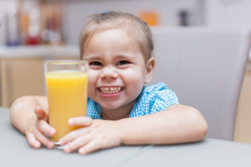 Dziecko dziewczyna z szkłem świeży sok pomarańczowy przy kuchnią fotografia stock