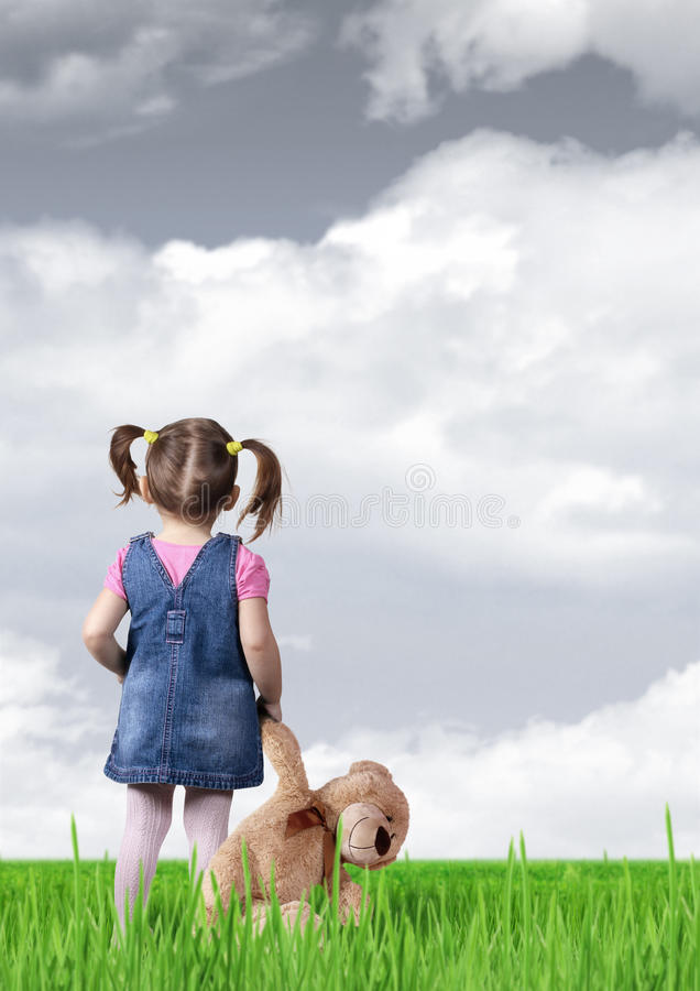 Dziecko dziewczyna z zabawka niedźwiedziem patrzeje w odległość, tylny widok zdjęcia stock