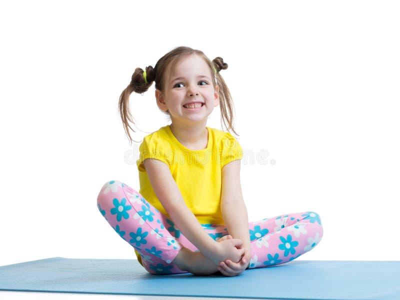 Dziecko dziewczyny ćwiczy joga, rozciąga w ćwiczeniu Dzieciak odizolowywający nad białym tłem obrazy royalty free