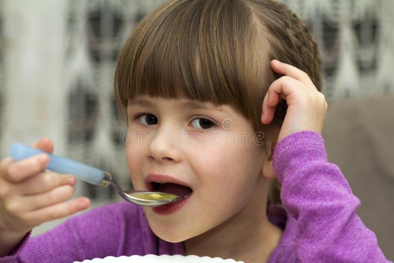 Dziecko dziewczyny łasowania polewka od talerza z łyżką obraz royalty free