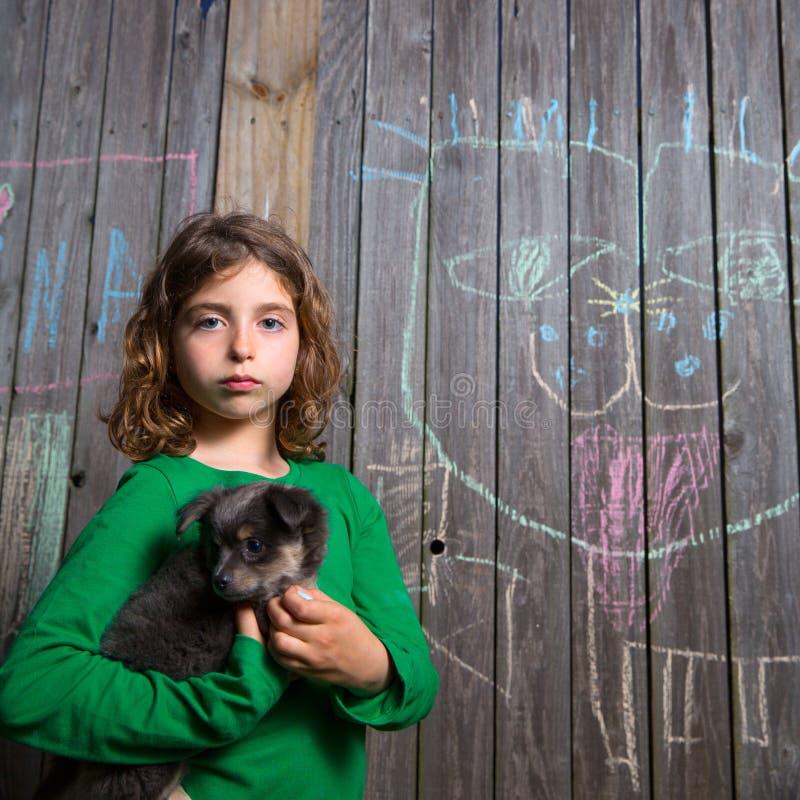 Dziecko dziewczyny mienia szczeniaka pies na podwórka drewna ogrodzeniu fotografia stock