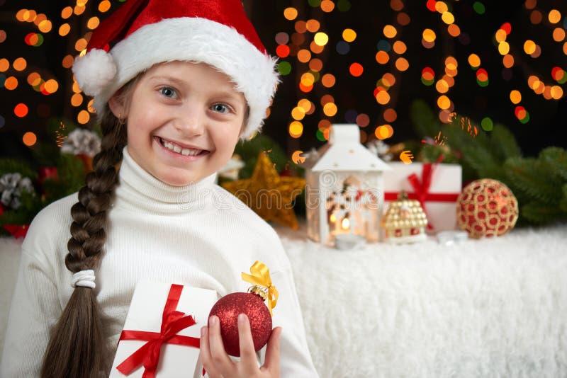 Dziecko dziewczyny portret na ciemnym tle z boże narodzenie dekoracją twarzy wyrażenie i szczęśliwe emocje, ubierał w Santa kapel zdjęcia royalty free
