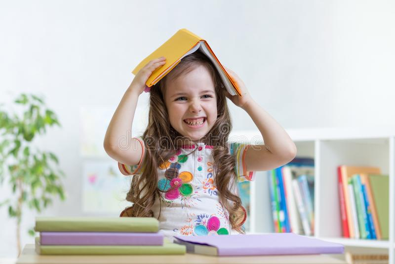 Dziecko dziewczyny uczeń w szkole trzyma książkę na jej głowie zdjęcia royalty free
