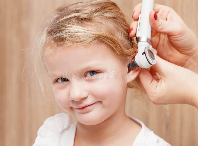 Dziecko ENT czek - doktorski egzamininuje ucho dziewczyna z oto troszkę obraz stock