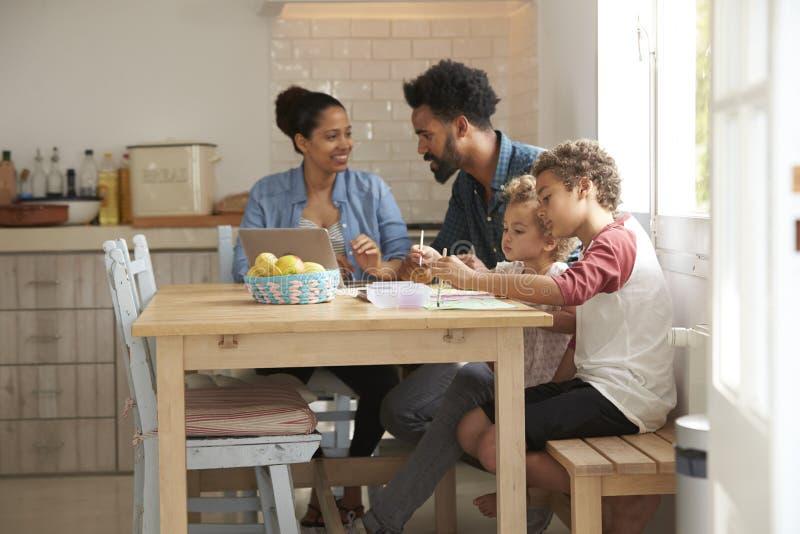 Dziecko farba Przy Kuchennym stołem Jak rodzica spojrzenie Przy laptopem zdjęcia royalty free