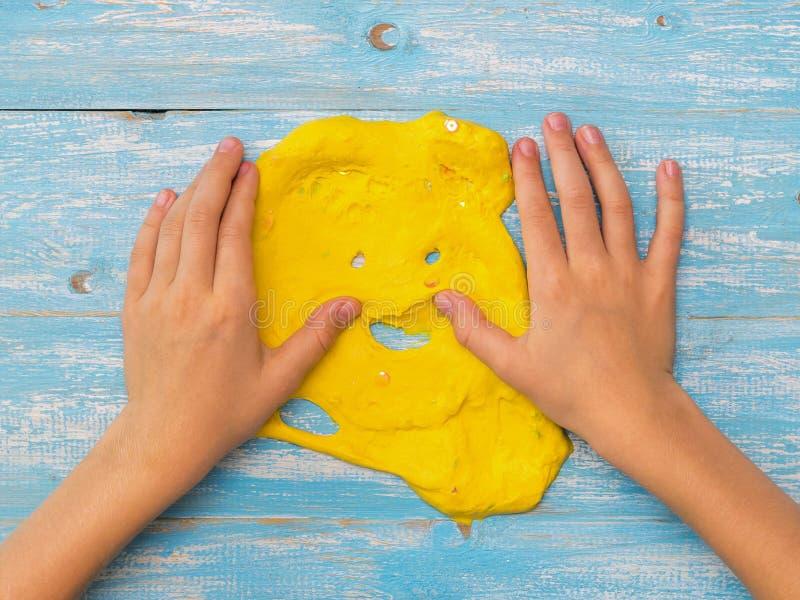 Dziecko gładzi ręka kolor żółtego szlamowego na błękitnym stole zdjęcia royalty free