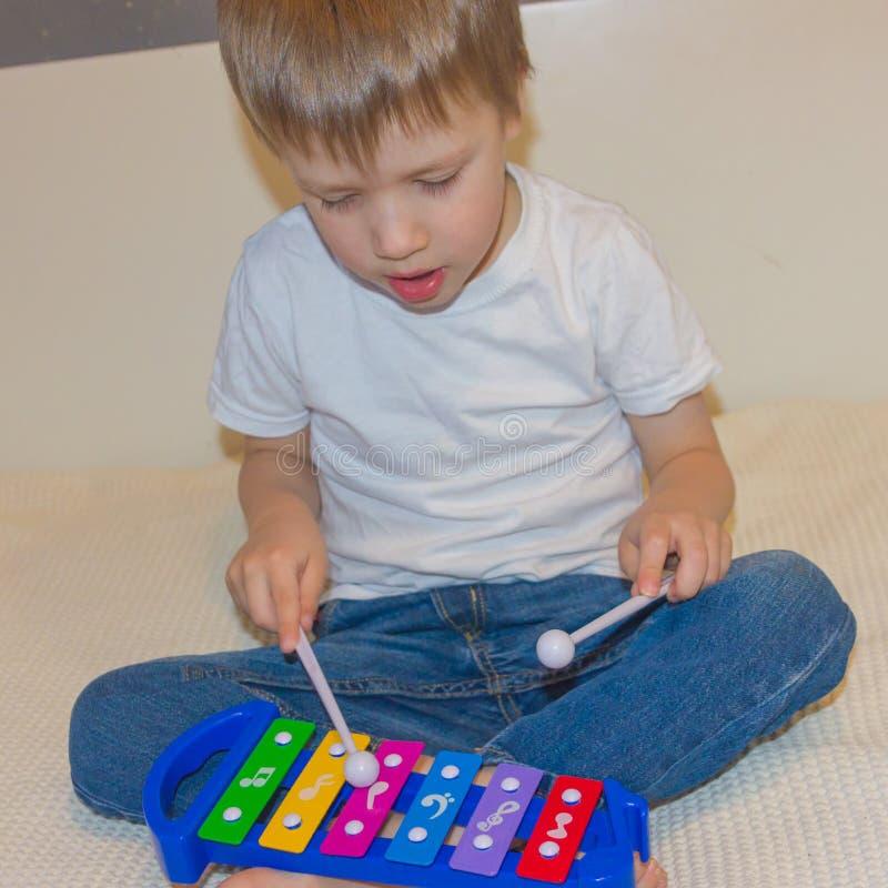 Dziecko i ksylofon Chłopiec puka jego chopsticks na xyloph obraz stock