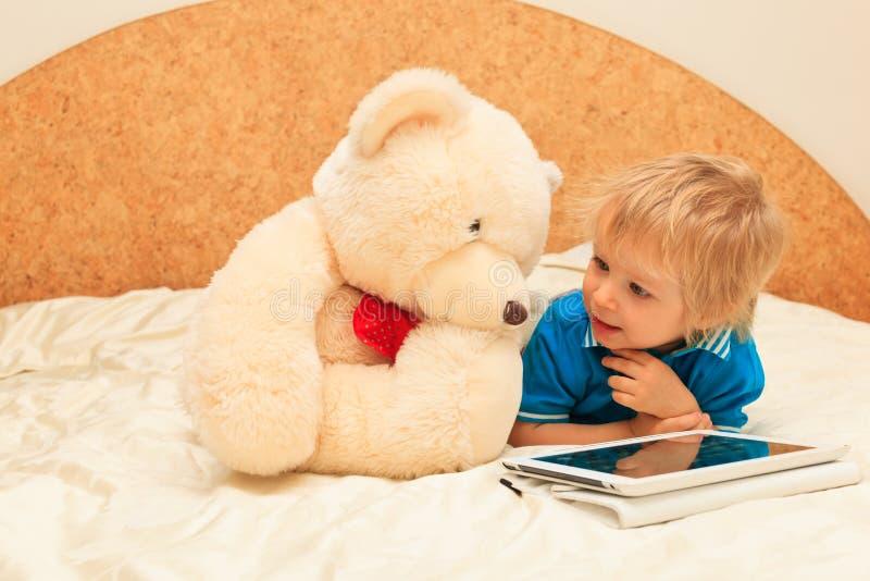 Dziecko i miś pluszowy z dotyka ochraniaczem obraz royalty free