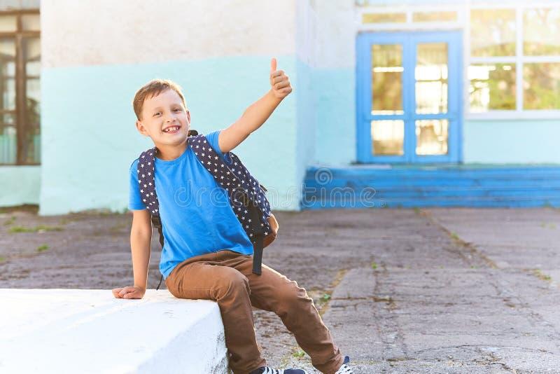 Dziecko i?? szko?a chłopiec uczeń iść szkoła w ranku szczęśliwy dziecko z teczką wewnątrz na jego plecy i podręczniki zdjęcie royalty free