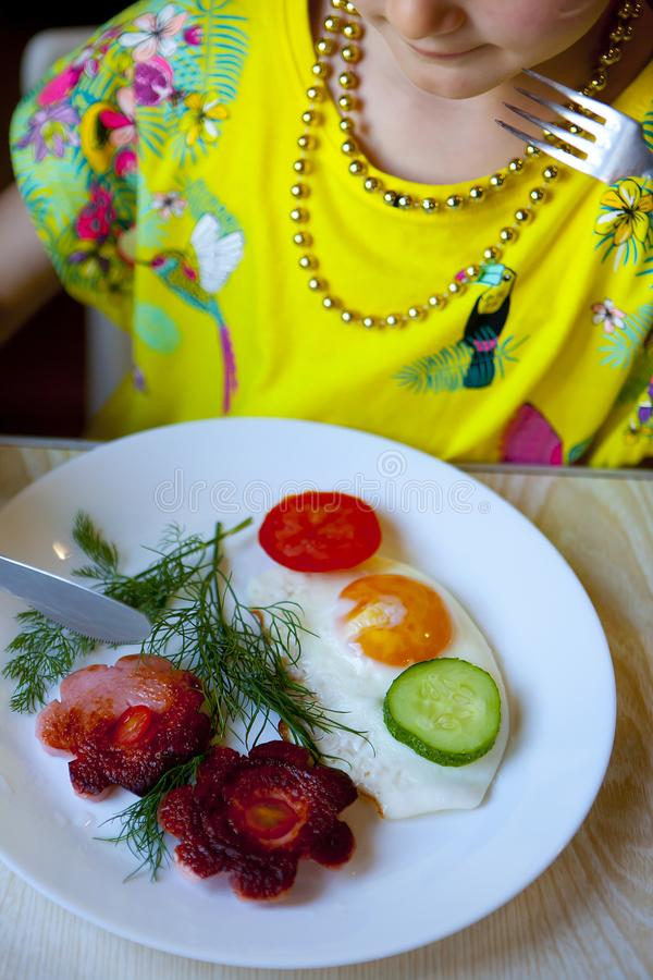 Dziecko je od biały talerz gramolących się jajek z kiełbasą, warzywami i ziele, Rozdrapani jajka przygotowywający w postaci obrazy stock