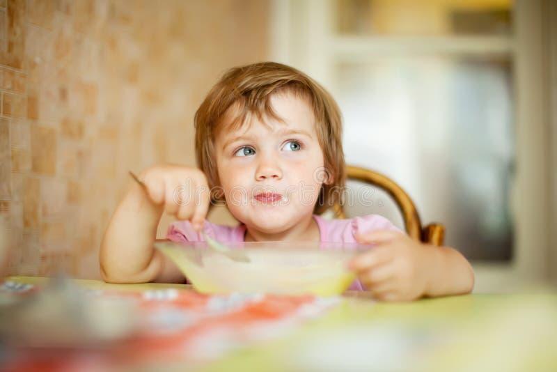 Dziecko je od talerza z łyżką fotografia stock
