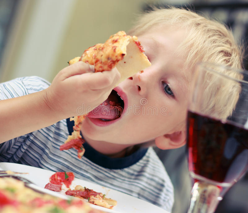 Dziecko je pizzę w cafeÑŽ obrazy royalty free