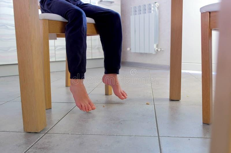 Dziecko je przy stołem i rozdrobni kukurydzanych płatki na podłodze Nogi i podłoga w górę zdjęcia royalty free
