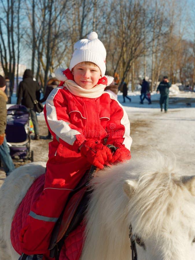 Dziecko jedzie konika outside w zimie obrazy stock