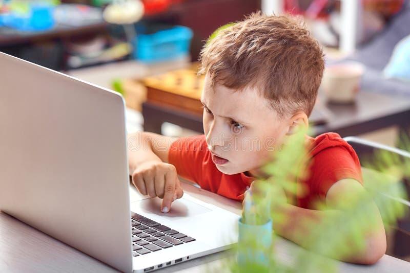 Dziecko jest przyglądający dla informacji o internecie przez laptopu samopoznanie w domu, robić pracie domowej Uważnie czytać obraz stock
