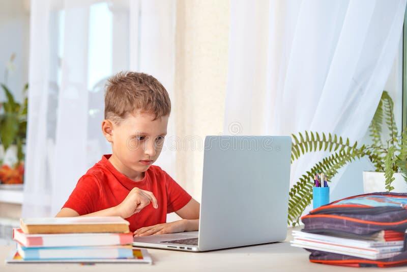 Dziecko jest przyglądający dla informacji o internecie przez laptopu samopoznanie w domu, robić pracie domowej Uważnie czytać obraz royalty free