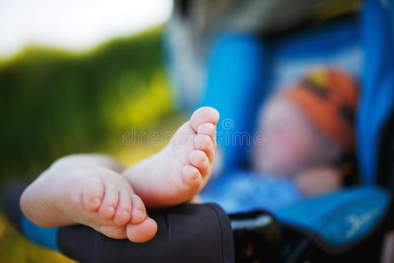 Dziecko kłama w spacerowiczu bosym Zbliżenie pięty dziecko baby feet Bosy w kareciani kłamstwa Pięty, palec u nogi i cieki zdjęcia stock
