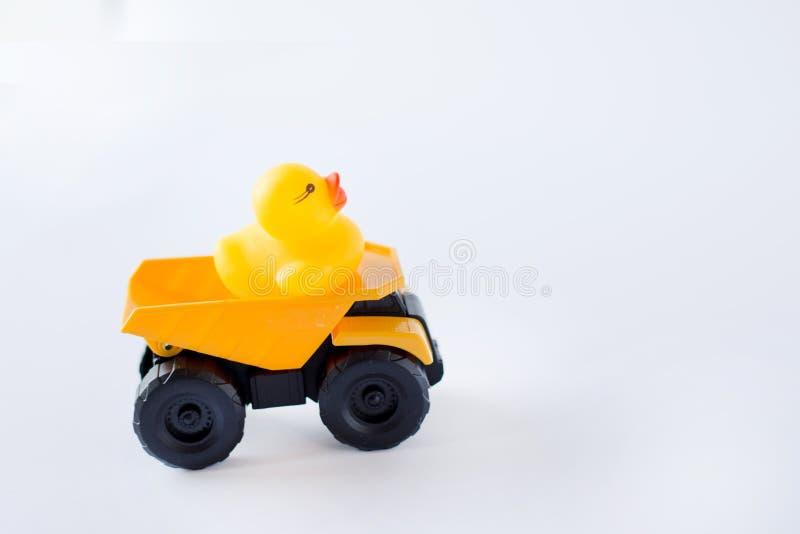 Dziecko kaczka na żółtym samochodzie odizolowywającym na białym tle kosmos kopii Pojęcie dzieciństwo zdjęcia stock
