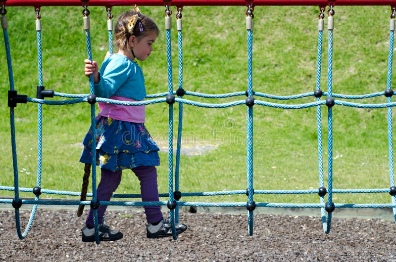 Dziecko krzyżuje nad zawieszenie mostem w boisku obraz stock