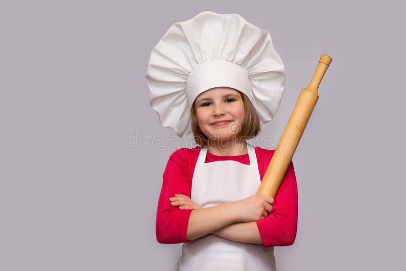 Dziecko kucharz Szczęśliwa mała dziewczynka w szefa kuchni mundurze trzyma tocznej szpilki odizolowywa na białym tle fotografia stock