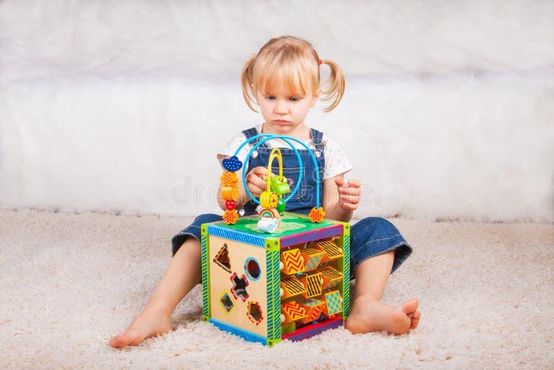 Dziecko mała dziewczynka bawić się z edukacyjną zabawką w pepinierze lub domu fotografia royalty free
