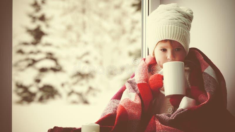 Dziecko mała dziewczynka z filiżanką gorąca herbata przy nadokiennym i patrzeć fotografia royalty free