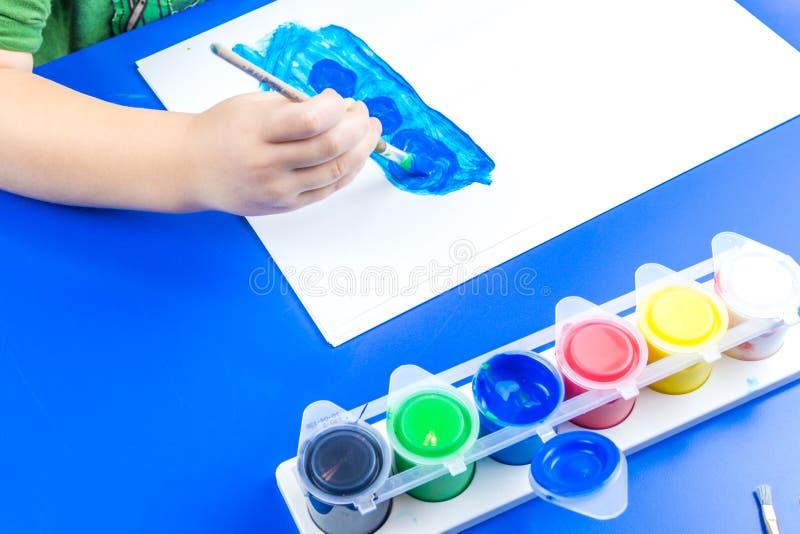 Dziecko maluje obrazek z tempera farbami obrazy royalty free