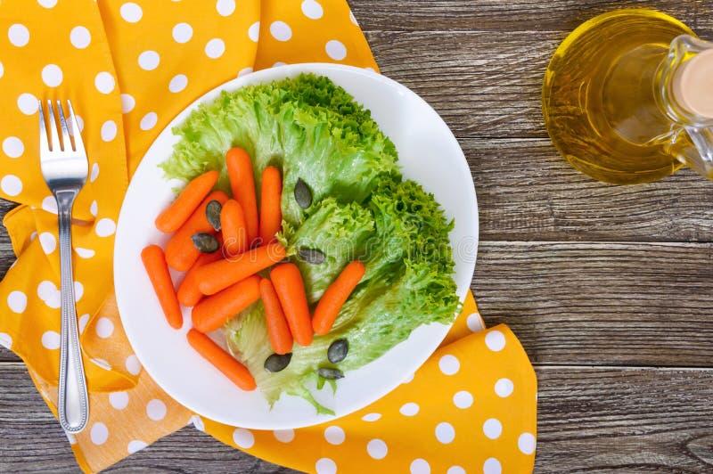 dziecko marchewki odizolowywali Mała marchewka z sałatą opuszcza na białym ceramicznym talerzu fotografia royalty free