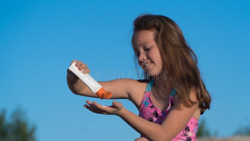 dziecko na plażę Śmietanka od sunburn błękitny butelki ochrony ochronny słońca sunscreen zdjęcia stock