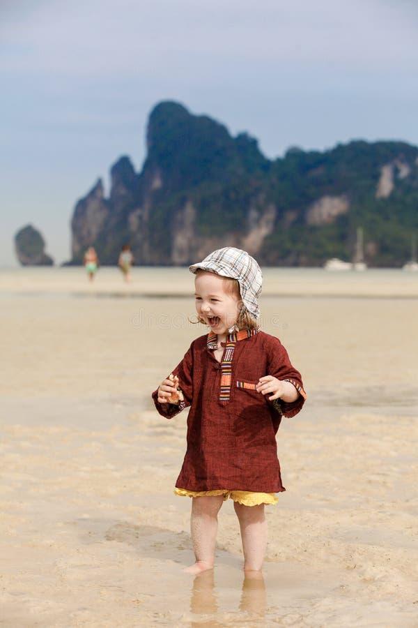 Dziecko na tropikalnej plaży, je chleb zdjęcie stock
