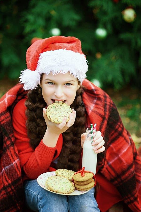 Dziecko napojów mleko od butelki i łasowań ciastek Uśmiecha się dziewczyny czekanie dla boże narodzenia w drewnie fotografia royalty free