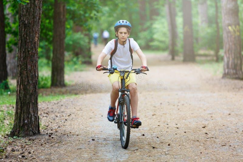 Dziecko nastolatek na rowerowej przejażdżce w lesie przy wiosną lub latem Szczęśliwa uśmiechnięta chłopiec jeździć na rowerze out fotografia royalty free